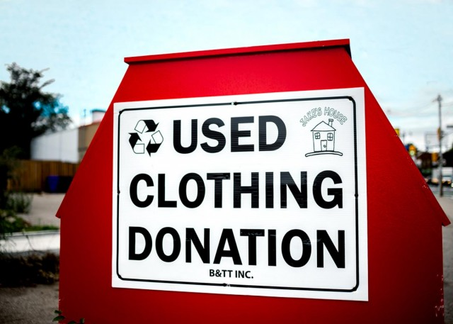 "big, red clothing donation bin outside saying ""Used Clothing Donation"""
