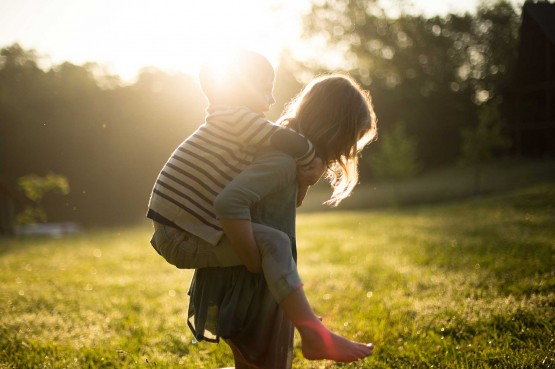 boy wearing striped shirt piggybacking on woman wearing in park at golden hour