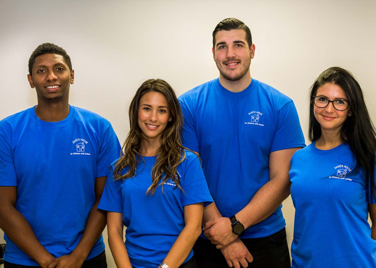 a team of four people in blue tshirts with the jakes house logo