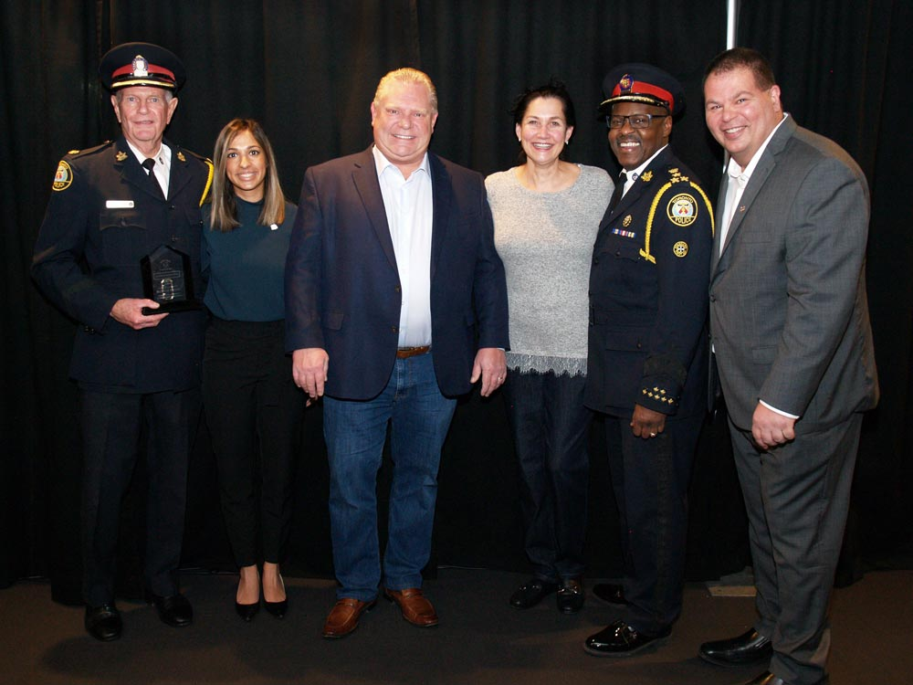 group photo of police officers event guests and doug ford