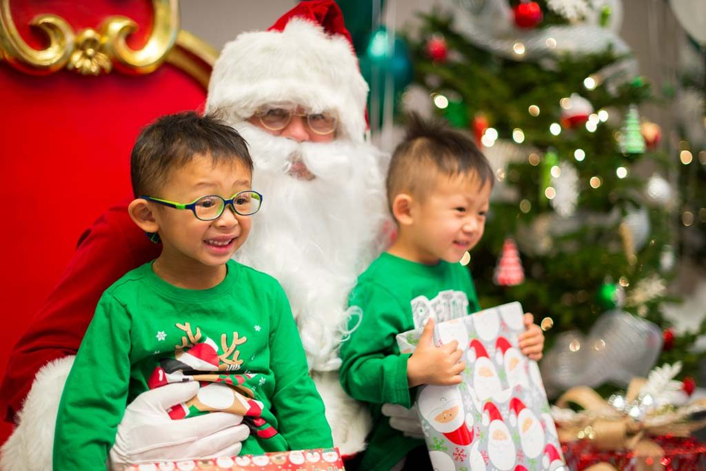 Two smiling children in green sweaters sitting on Santa's knee and holding wrapped presents