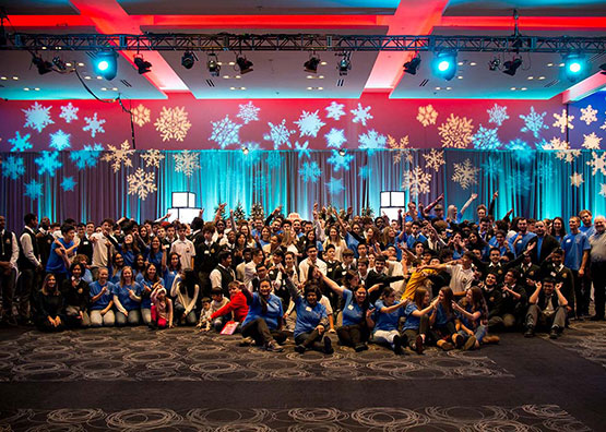 A group photo at a Holiday party lit by red and blue lights, red balloons, and snow flake projections.