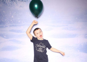 Boy with an expression of excitement holding a green balloon at a holiday party photo booth