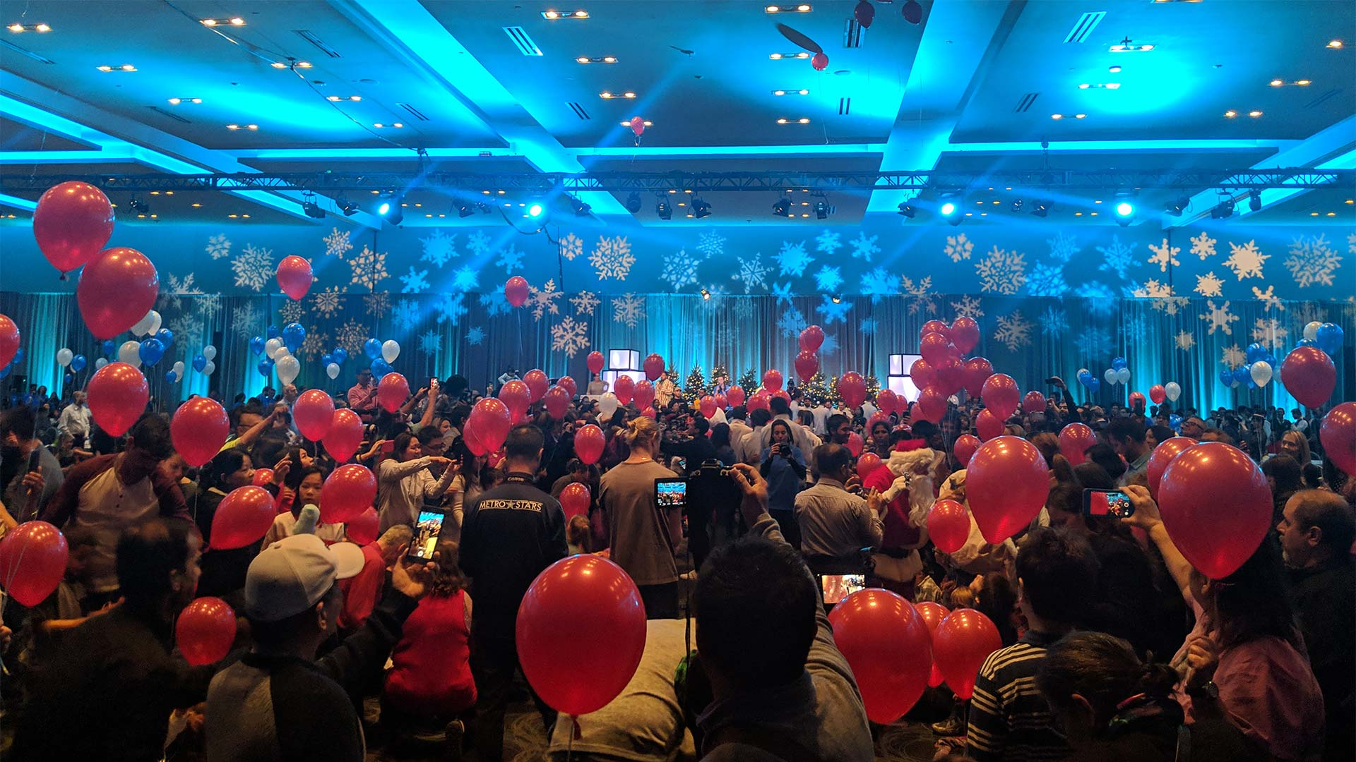 A grand holiday party in a large event space with blue lights, red balloons, and snow flake projections.