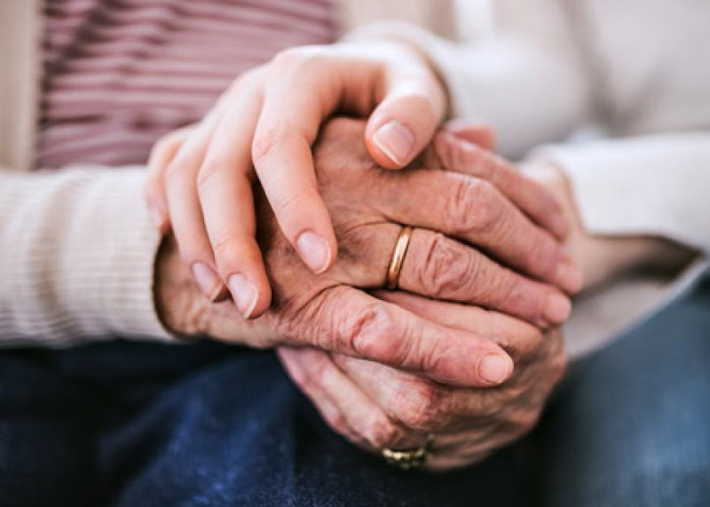 younger hands kindly holding an elder man's hands in support