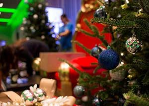 Close up of a christmas tree with a blue and silver ornaments while a holiday party goes on in the background