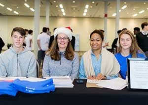 Four Jake's House volunteers sit at a registration table at a holiday charity event.