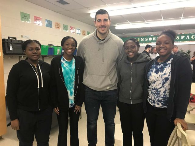 a tall man posing for a picture with four students in a classroom
