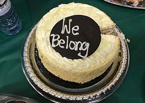 """a cake with the words """"we belong"""" written on it in icing"""