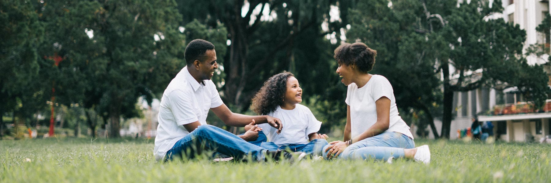 family of mom, dad and young daughter sitting on grass laughing