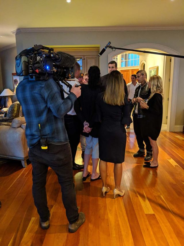 A film crew filming a group of formally dressed people in a reception room