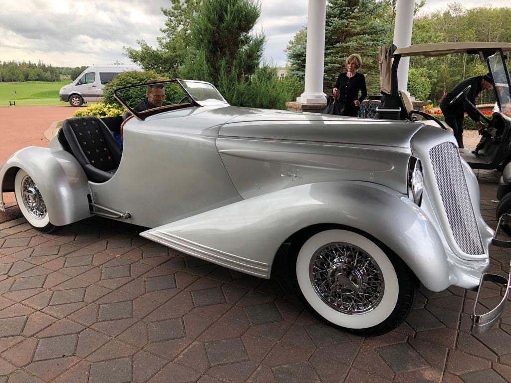 A silver Bad Chad custom hot rod car parked in front of a golf resort  entrance 89ea23749
