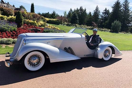 Bad Chad posing and smiling in a silver custom hot rod car on a sunny day