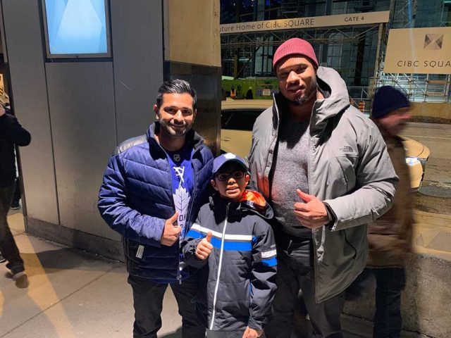 """A boy and two men in winter clothes smiling and giving a """"thumbs up"""" at a hockey game"""
