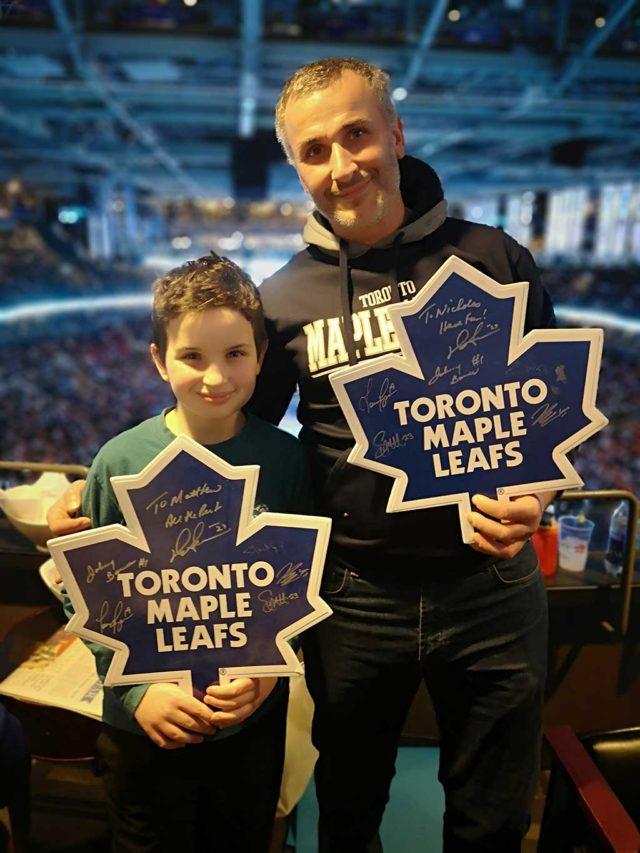 A man and a boy holding Toronto Maple Leafs cutouts at a hockey game