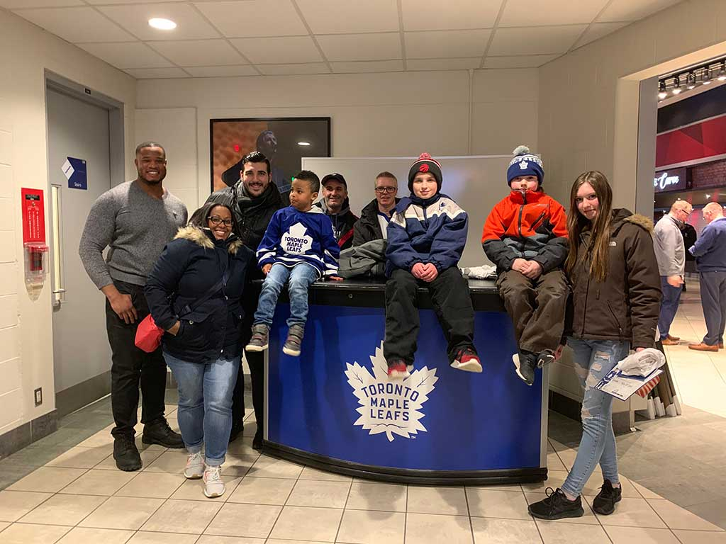 A group of people in winter clothes posing around a Toronto Maple Leafs branded desk