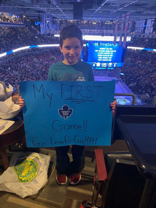 A boy holding up a hand-made cardboard sign at a hockey game