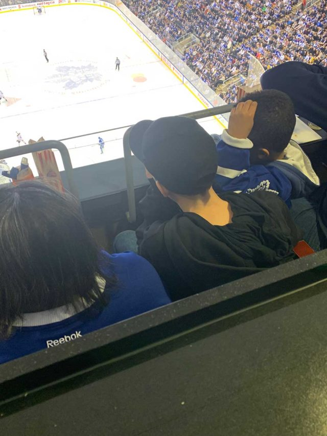 a group of boys looking down at the ice from seats at an NHL hockey game