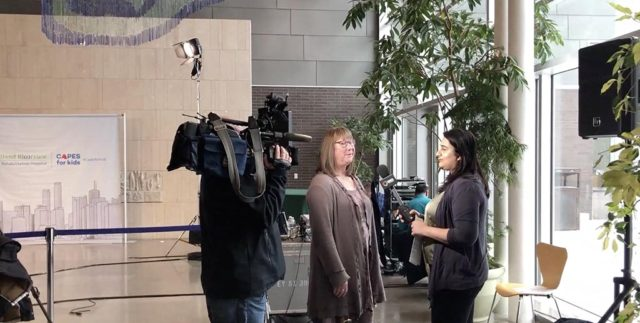 a woman being interviewed by a TV news anchor at a press release