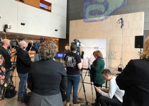 news cameras focused on a woman making an announcement at a press release
