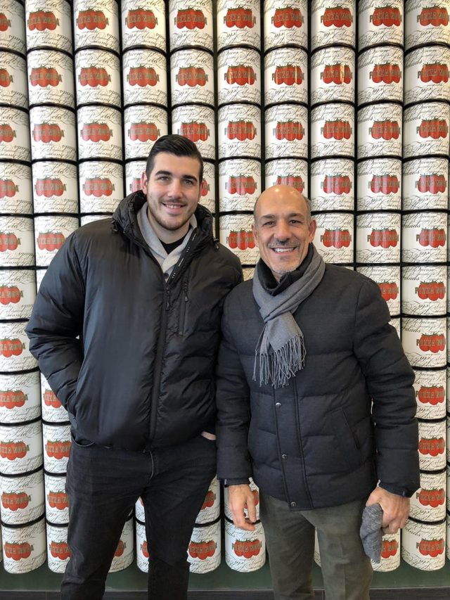 two men posing in front of a wall of stacked canned tomatoes