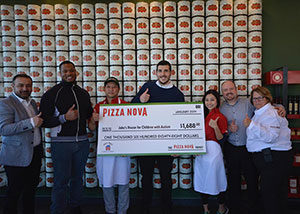 a group of people posing with a giant-sized cheque for a charity donation