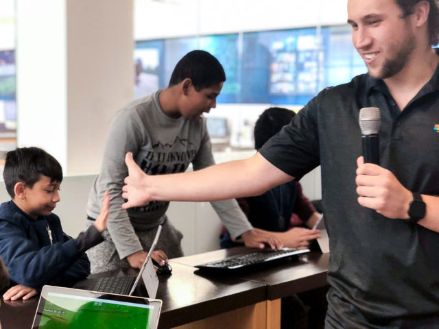 a man with a microphone high fives a kid at a Minecraft event