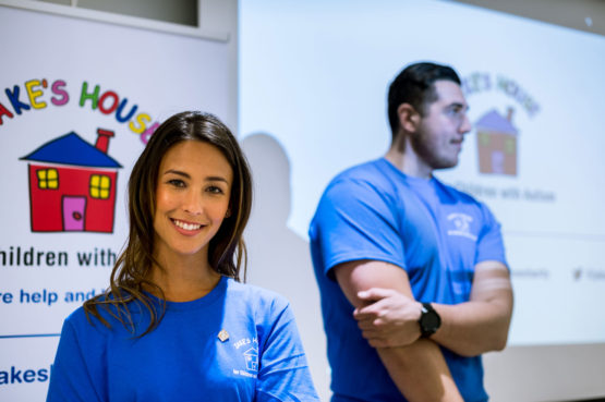 two smiling volunteers in blue t-shirts making a charity presentation