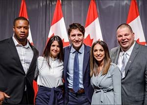 Four members of the Jake's House team posing with Prime Minister Justin Trudeau in front of Canadian flags