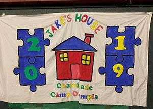 a hand-painted cloth banner for Jake's House Chaminade Camp Olympics 2019
