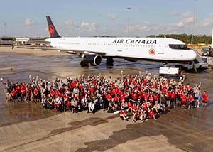 A large group of charity volunteers in red shirts posed outside an Air Canada plane on the tarmac