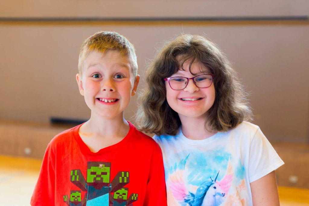 portrait of young boy wearing red shirt and girl wearing white shirt smiling