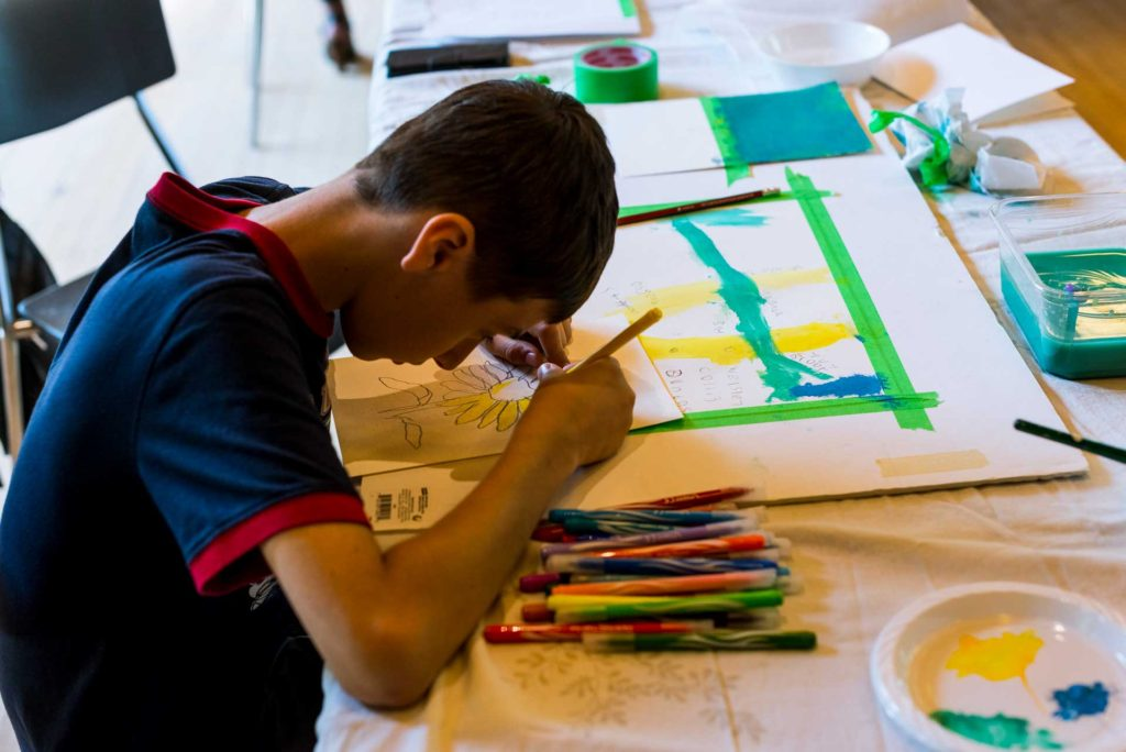 boy leaning forward over drawing of sunflower on table with pencil