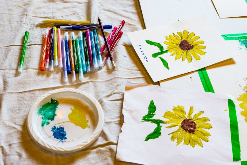 two paintings of sunflowers with pile of markers and pencils