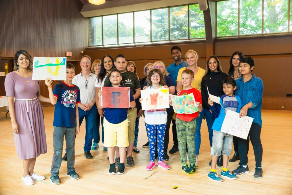 group photo of children holding up artwork with parents in gymnasium