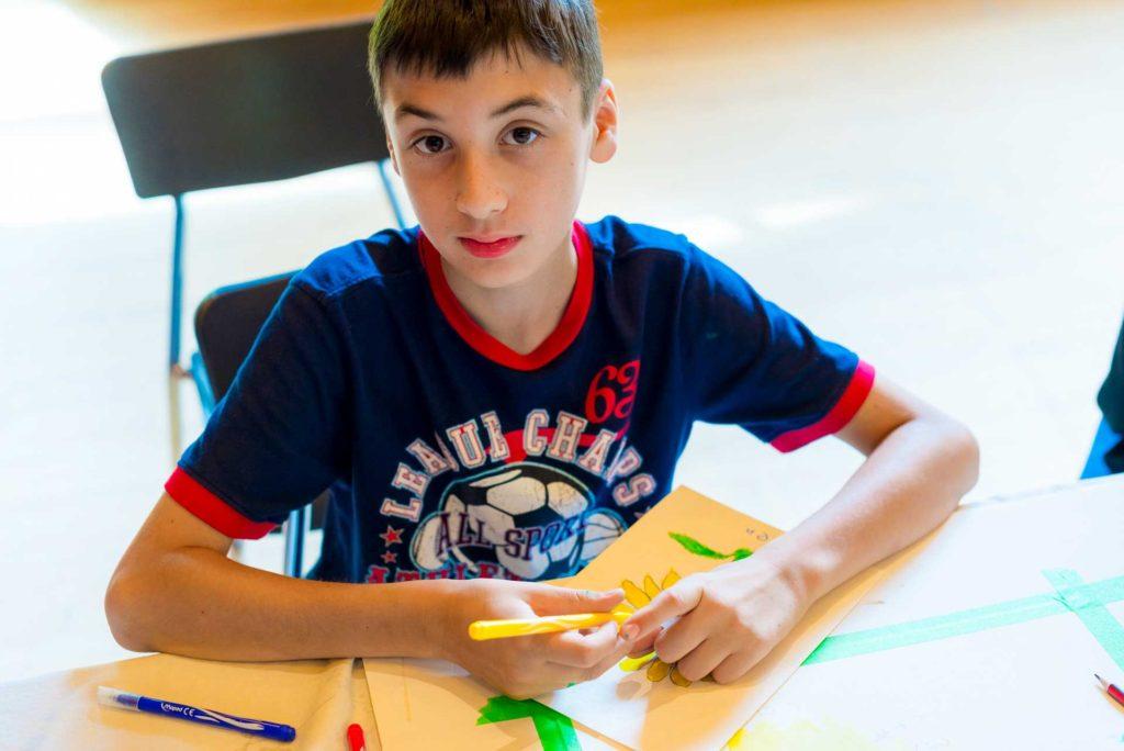 boy sitting at table in dark blue shirt holding marker over artwork