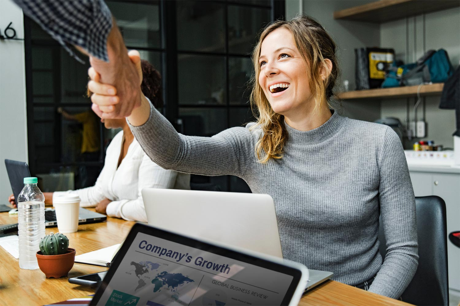 young woman smiling while shaking business man's hand over Company Growth presentation on laptop