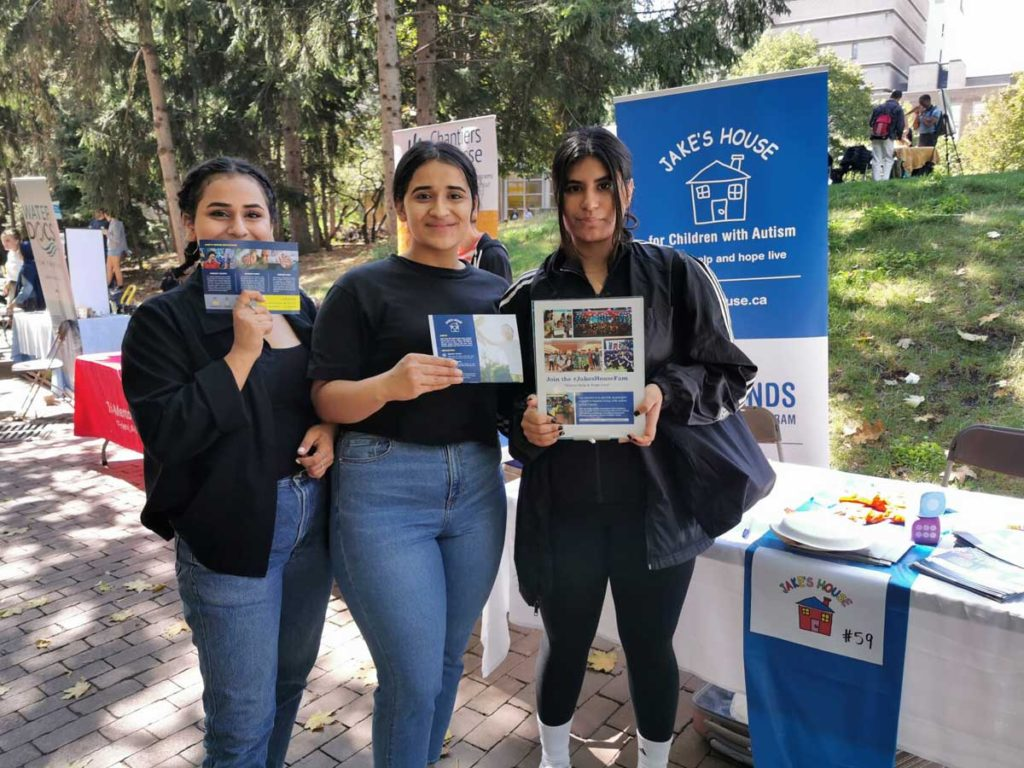 three women holding jake's house flyers in front of table outside