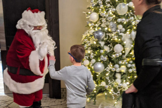 young boy high-fiving Santa Claus