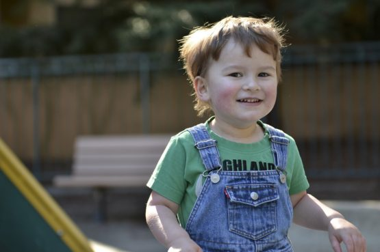 Signs your child has autism Boy in overalls